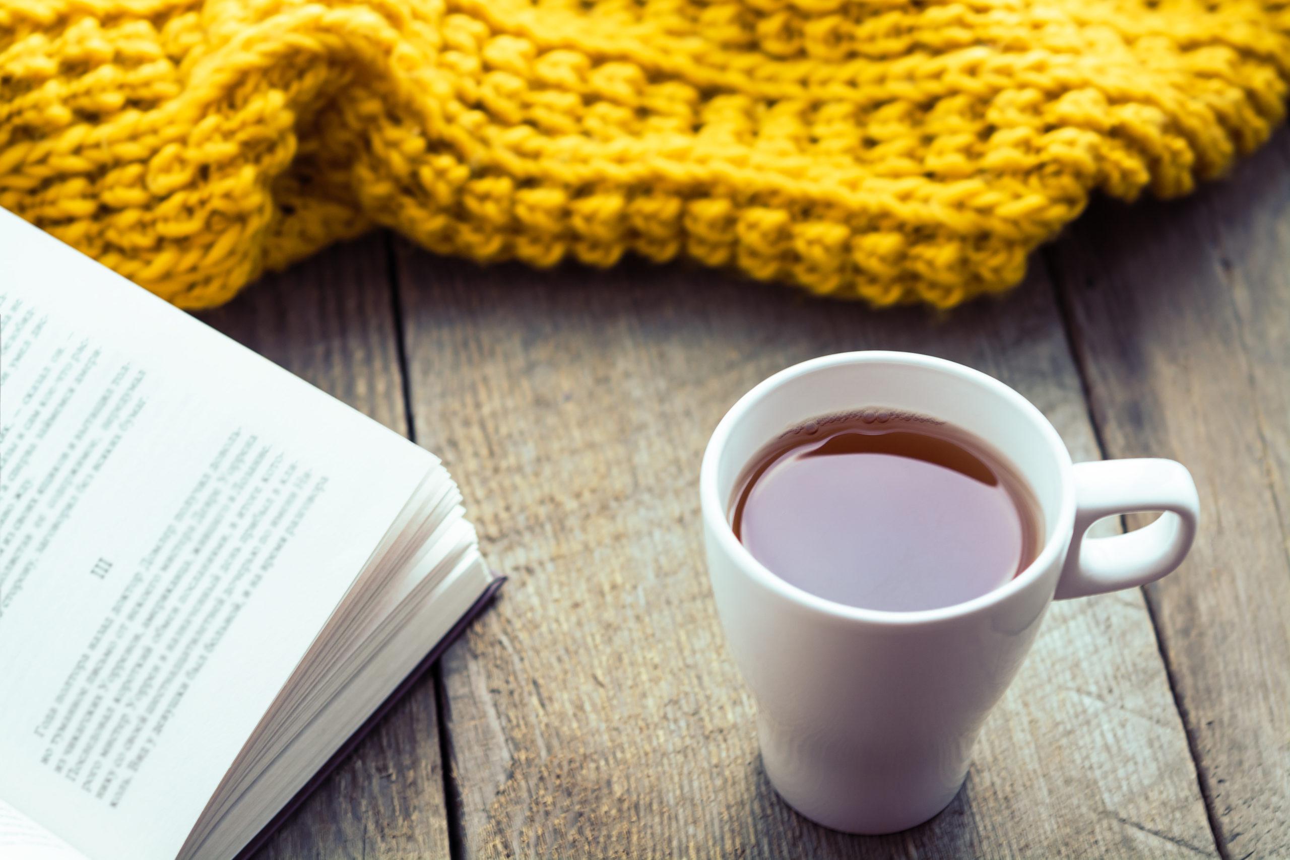 En kopp te framför en öppen bok och gul scarf.