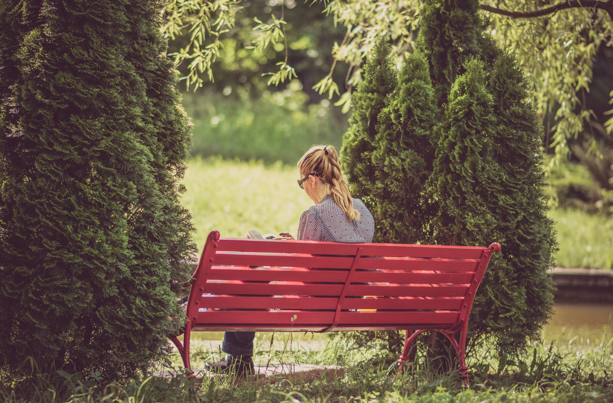 Kvinna sitter och läser på bänk i naturen
